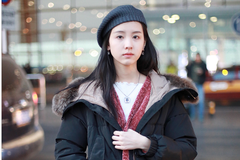 陈都灵穿黑色长款羽绒度内搭橘红色长款大衣现身机场打扮清新时尚