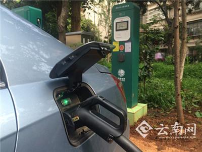 一辆吉利电动汽车的车主正在使用充电桩给自己的电动汽车充电.