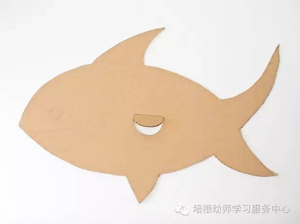 在纸箱上画上鲨鱼,然后剪下鲨鱼的轮廓,在鱼鳍位置留一个小洞哦