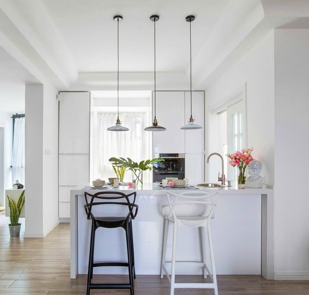 开敞式的厨房与客厅融为一体,餐桌上吊灯的设计,让人有种置身餐厅的