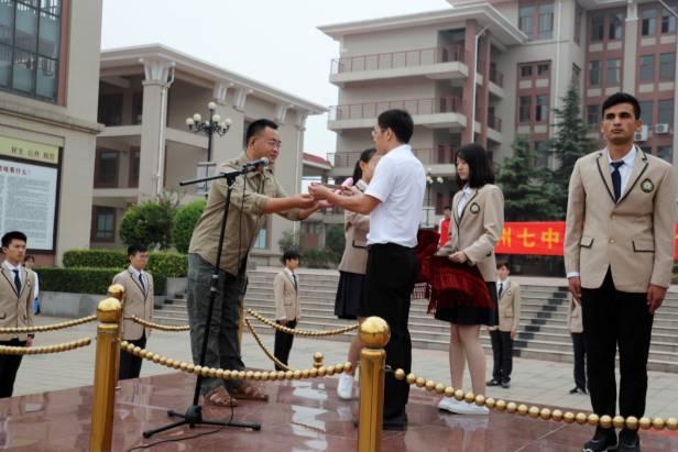 家长在开学典礼上发表震撼性演讲后,将手中的戒尺交给了老师