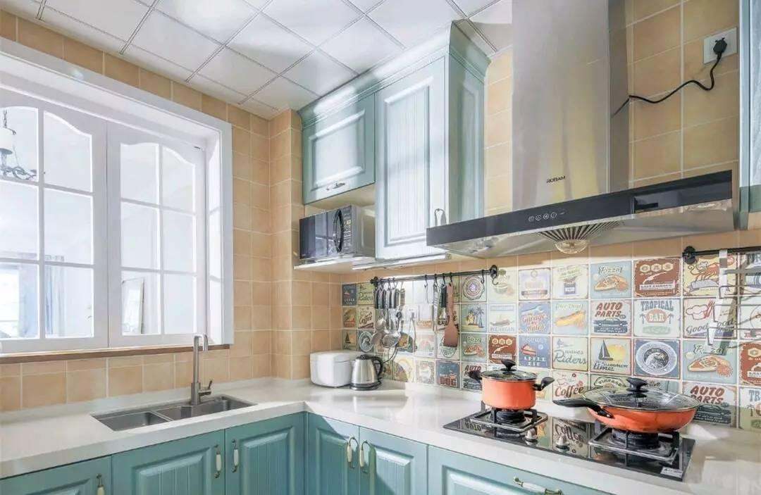 厨房操作台后方的墙面是创意图案的花砖,很美式,搭配上橄榄绿的橱柜