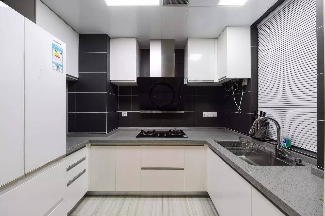 黑色的瓷砖,结合白色的橱柜,灰色的台面,营造出了一个黑白灰的现代