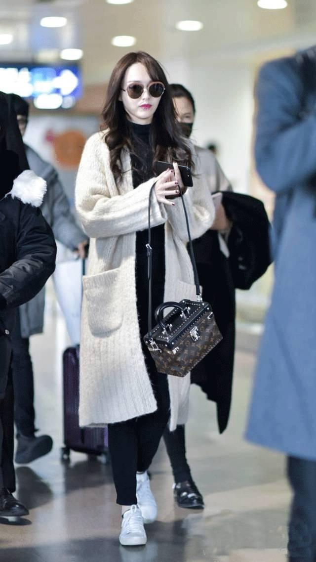 机场造型的热巴,用黑色针织开衫搭配过膝长靴.