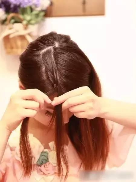 步骤四:分出来后,用手抓住左边分出来的刘海,把后面剩余的头发用皮筋图片