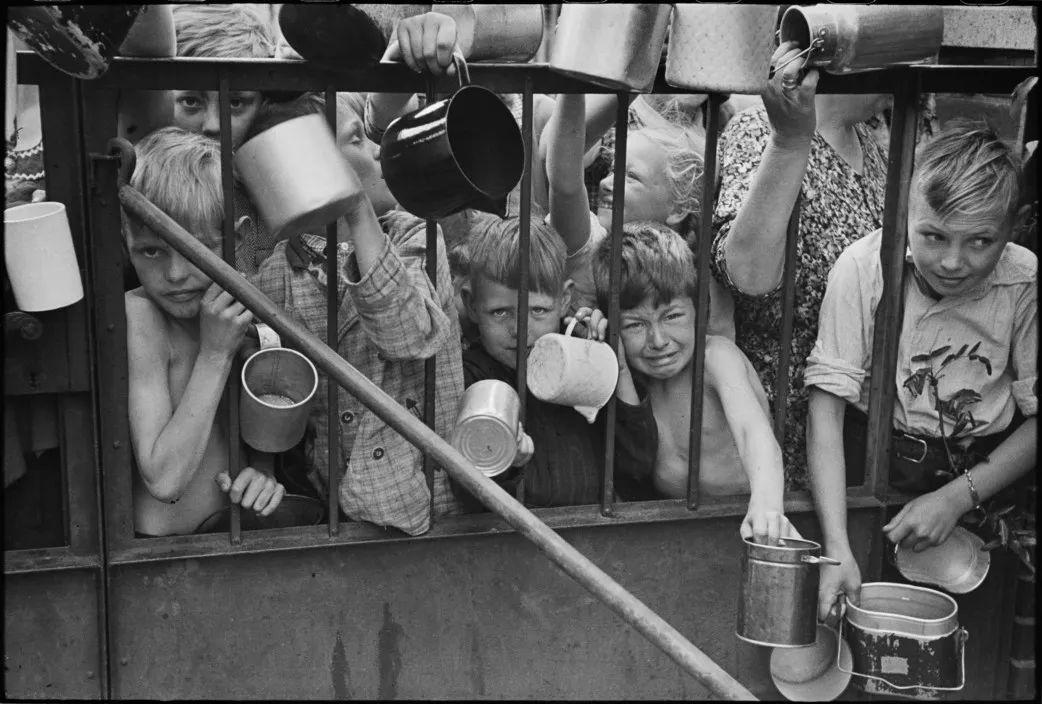 难民营里的儿童向盟军乞讨食物.