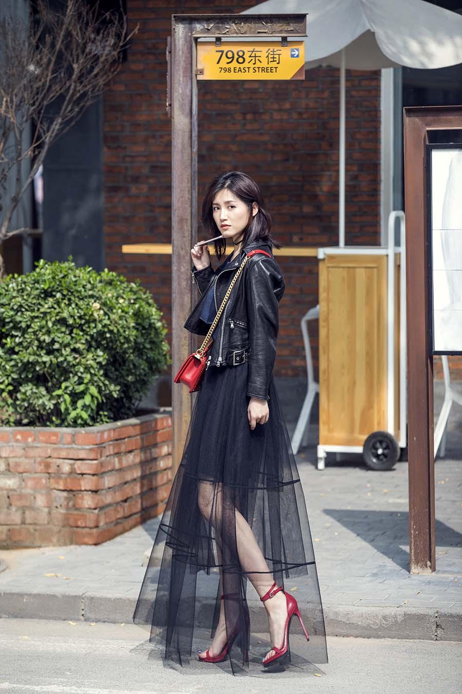 演员苏青曝光一组金属风街拍,照片中苏青身穿黑色皮衣,搭配黑纱长裙图片