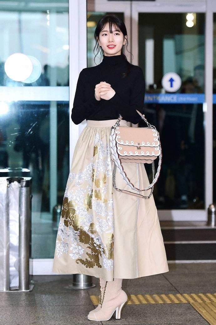 全身裸色系单品搭配黑色针织衫,不但衬托了长裙的华丽,半高领的设计