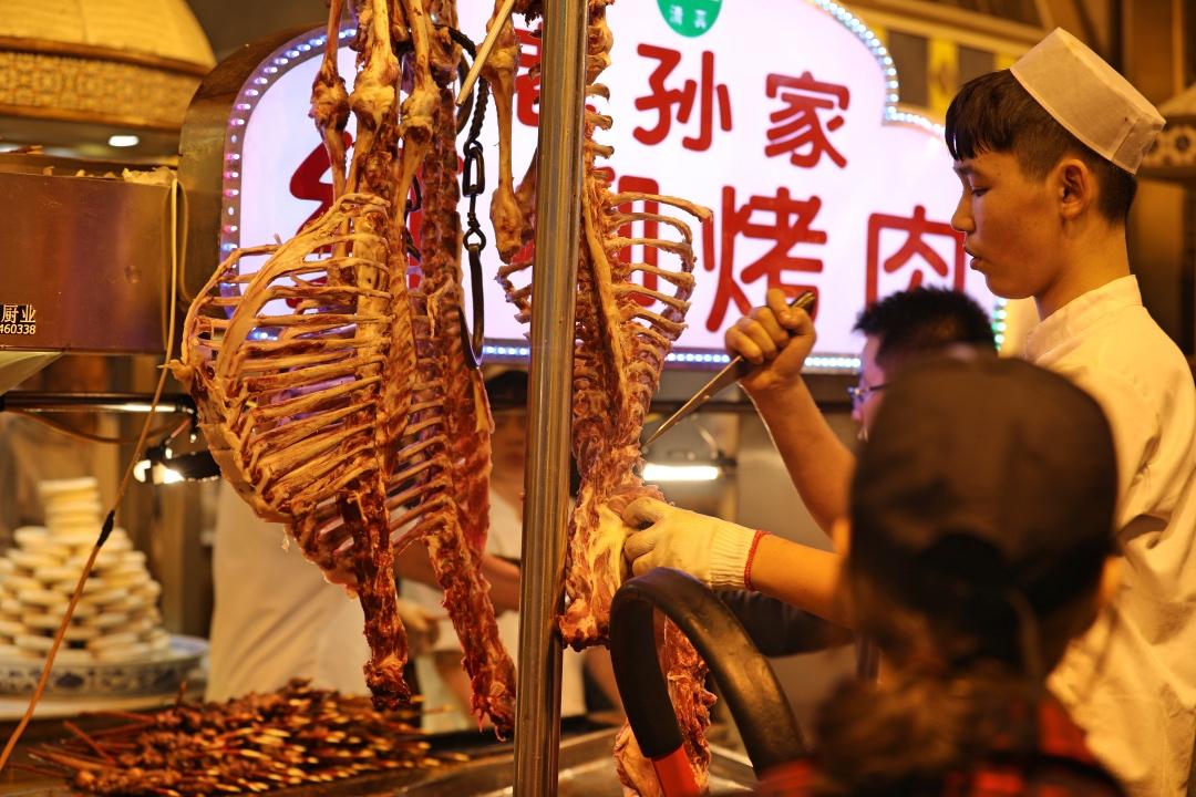 西安回民街人们习惯于挂着羊肉边切边烤,其乐融融