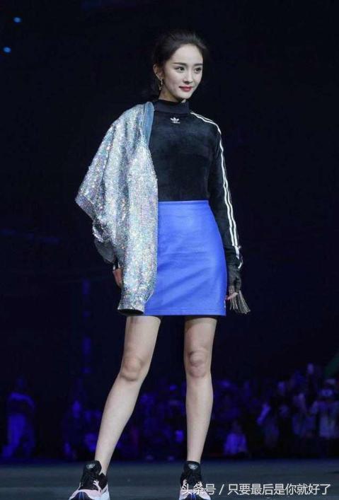 杨幂走秀造型,模仿模特将衣服挂在肩上,黑色上衣衬托出傲人上围.