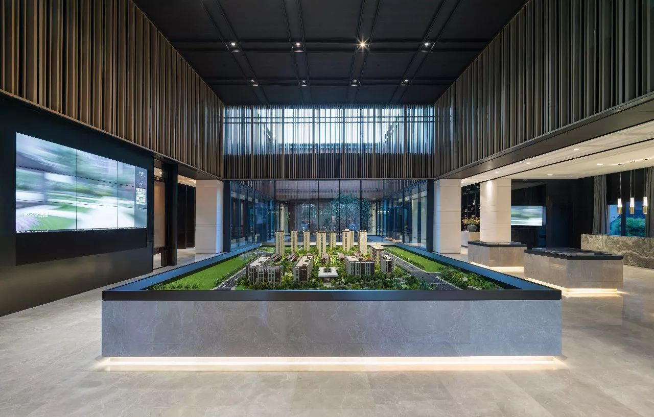 以模型区为中心的中庭空间 映衬在深色天花和精致的木质格栅之下 气度
