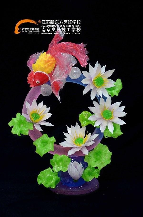 而在江苏新东方烹饪学校,说到糖,江苏新东方学子对它的推崇却不止于甜品,其实糖还可以来制作糖艺,糖艺制品色彩丰富绚丽,质感剔透,三维效果清晰,是西点行业中最奢华的展示品或装饰原料。江苏新东方学子运用自己的智慧制作出绚丽的糖艺制品金鱼戏荷。