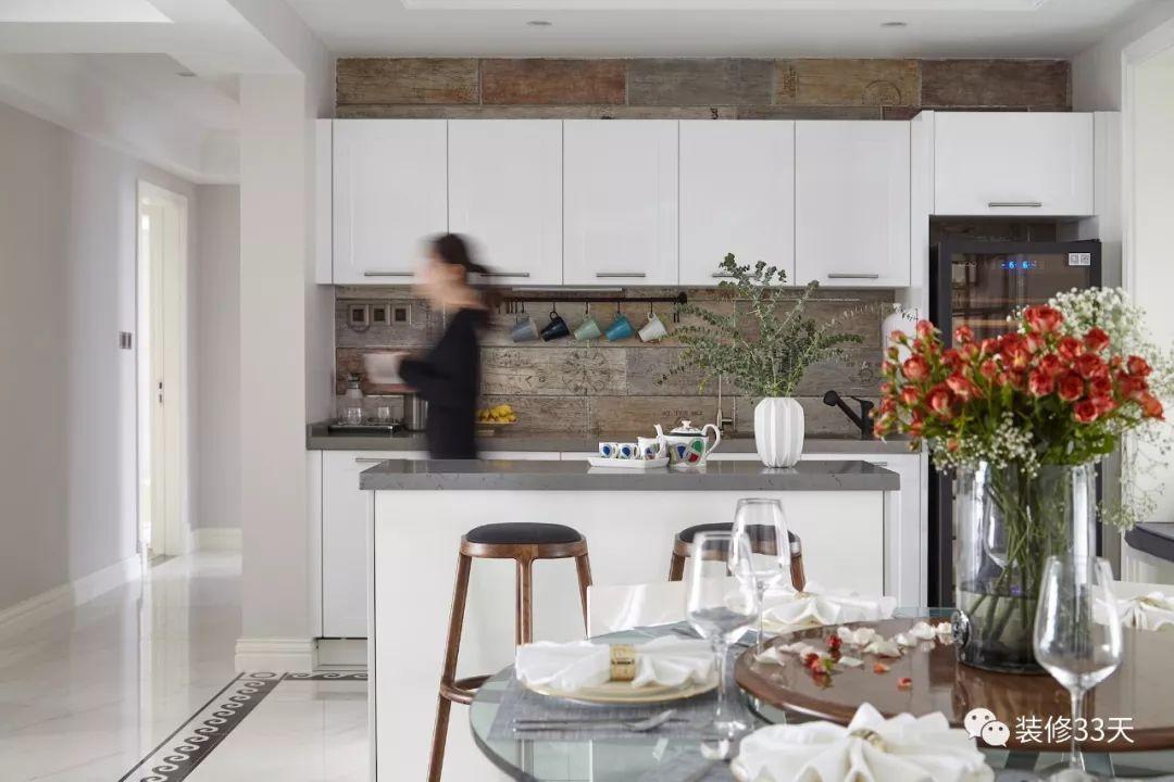 开放式西厨吧台与餐厅相邻,白色橱柜搭配海洋木纹墙砖,充满复古