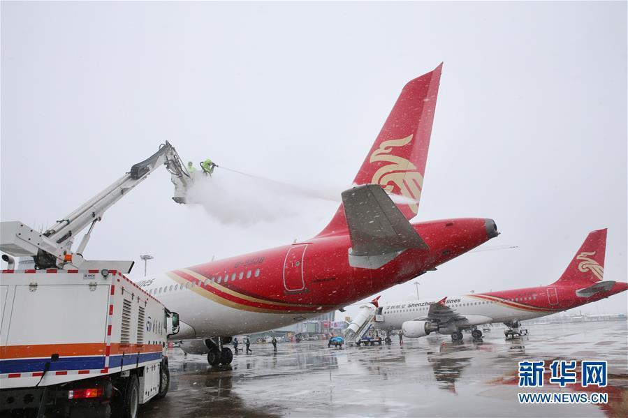 1月25日,在江苏南通兴东国际机场,工作人员冒雪进行客机除冰雪作业.