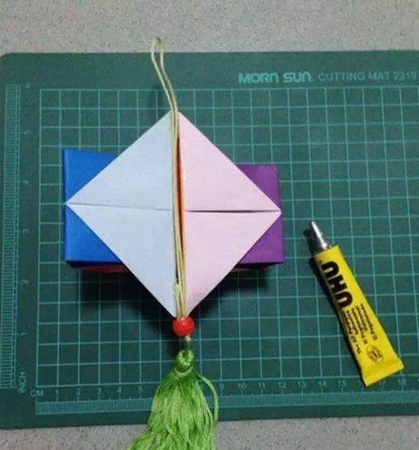美食 正文  制作步骤:准备正方形彩纸12张,彩绳等 对角折, 如图共做12