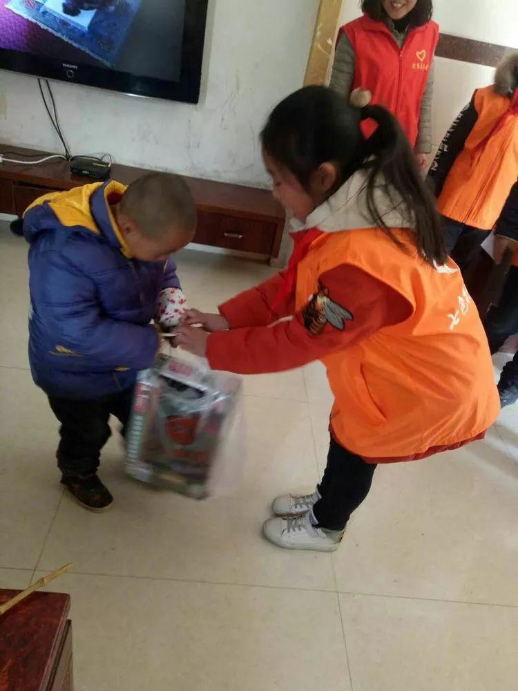 小志愿者们亲手做好了新年贺卡,带上小玩具,绘图本,来到残障儿童的家