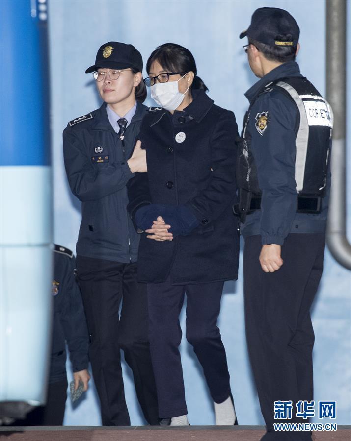 2月13日,在韩国首尔,崔顺实(中)出席庭审后准备离开首尔中央地方法院.图片
