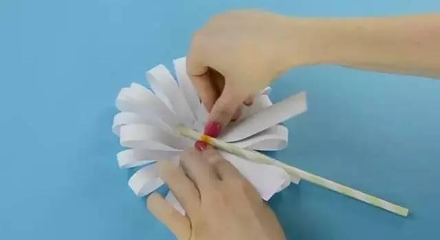 从黑色卡纸上裁剪下一个圆形纸片 然后全部纸条叠在一起做成花瓣状