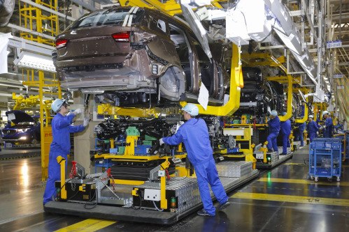 总装生产线上,装载着发动机的移动机器人全程跟随生产线上的工人对图片