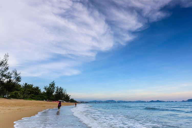岸上绿树如带,构成三亚海滨风景区美丽动人的海岸线; 海湾沙滩洁白