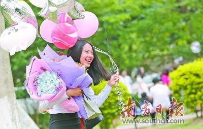 一手捧着鲜花、一手牵着气球的女生在镜头前露出灿烂的笑容.