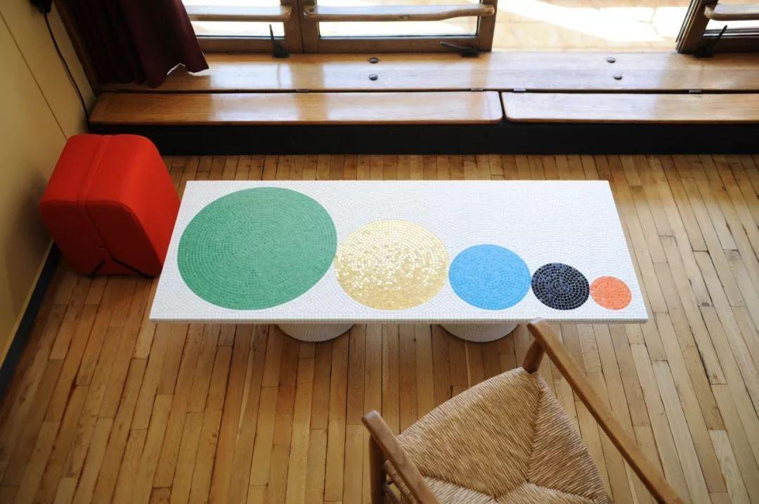 一张马赛克拼成的白色茶几 桌面是依次排列的五个圆圈图案 吊灯非常