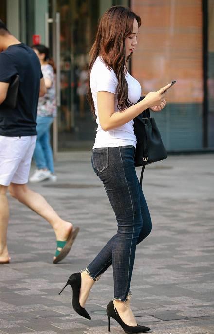 街拍: 白色紧身t恤搭配深色紧身牛仔裤, 身材丰满的黑色高跟鞋美女