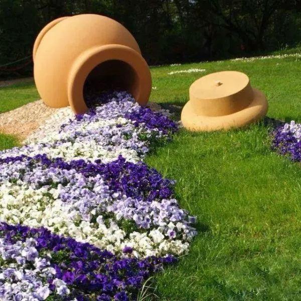 上面这个是一个非常简单的旧陶罐加上一些不同花色的小花,搭配成靓丽的花卉尽管,在草坪上形成独特的景象。 制作方法也是很简单的,将一些盆栽的花卉移栽到上,沿着陶罐的开口布置出一条河流般的花坛,陶罐倾斜摆放,看起来就像是从陶罐从溢出来,适合布置各色的矮牵牛、三色堇和一串红等植物。 2、多肉植物喷泉