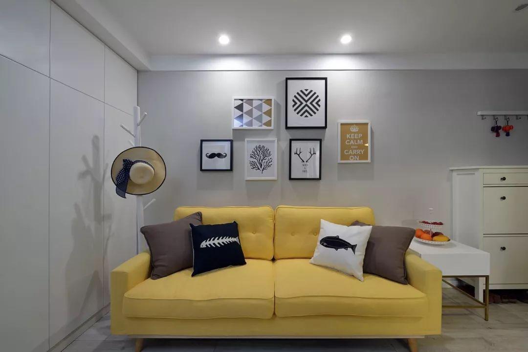 客厅沙发墙上挂一组装饰画,素黄色的布艺沙发,搭配侧边的一个落地挂图片