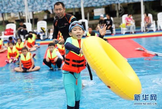 6月1日,小朋友在重庆涪陵红酒小镇水上乐园练习水上救援技能.
