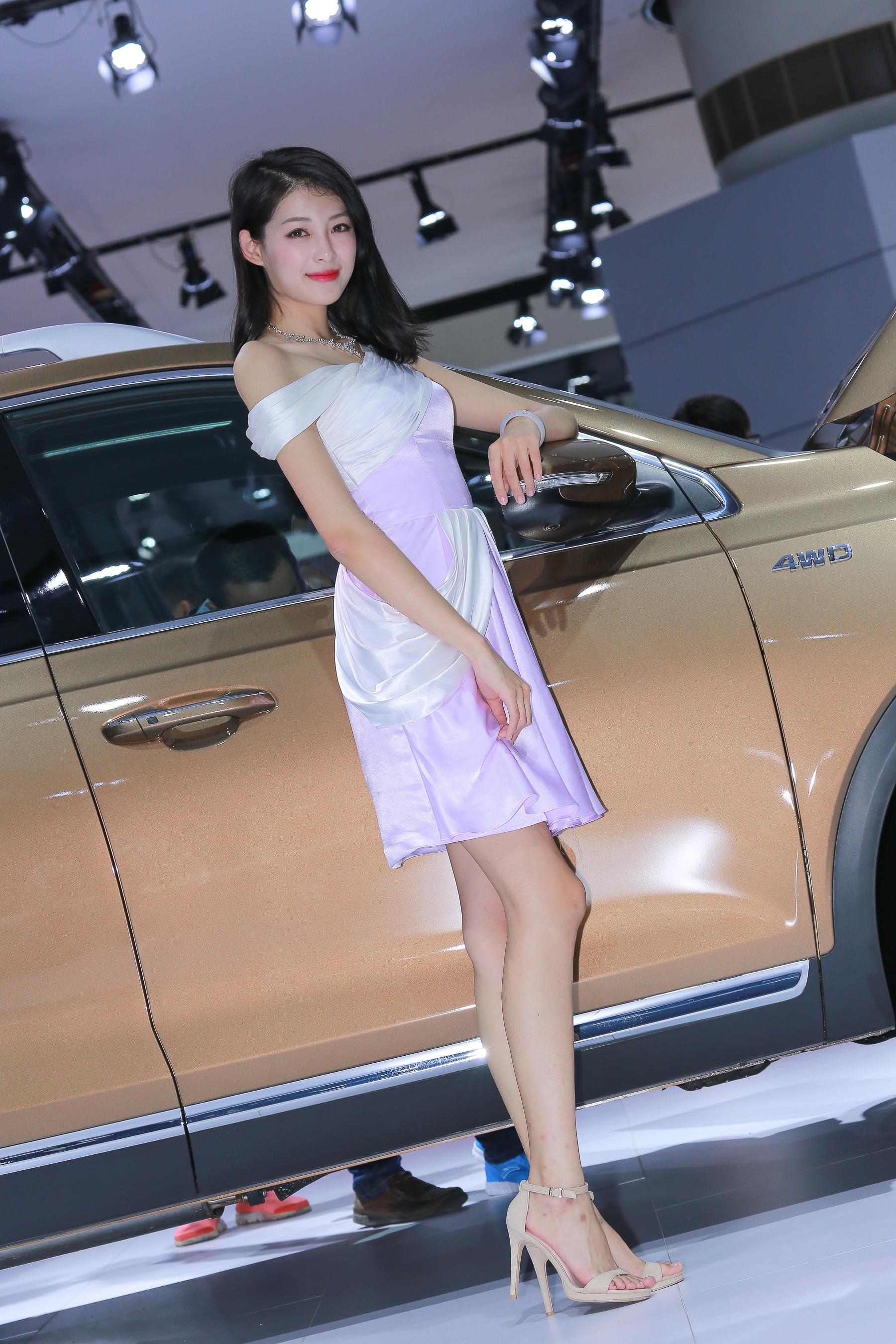 车展人像摄影:美丽的车模身材高挑,微笑可人,气质优雅