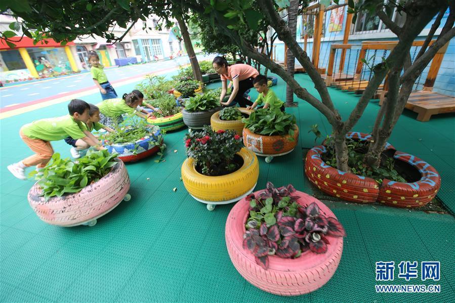 6月4日,湖北省襄阳市实验幼儿园的孩子们摆放由废旧轮胎制作的花盆.图片