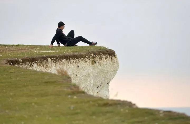 英国有一处悬崖,游客不顾阻拦悬崖边拍照
