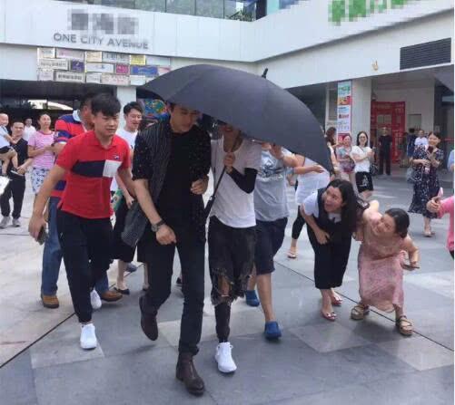 靳东被助理撑伞遮住脸 女粉丝蹲下身