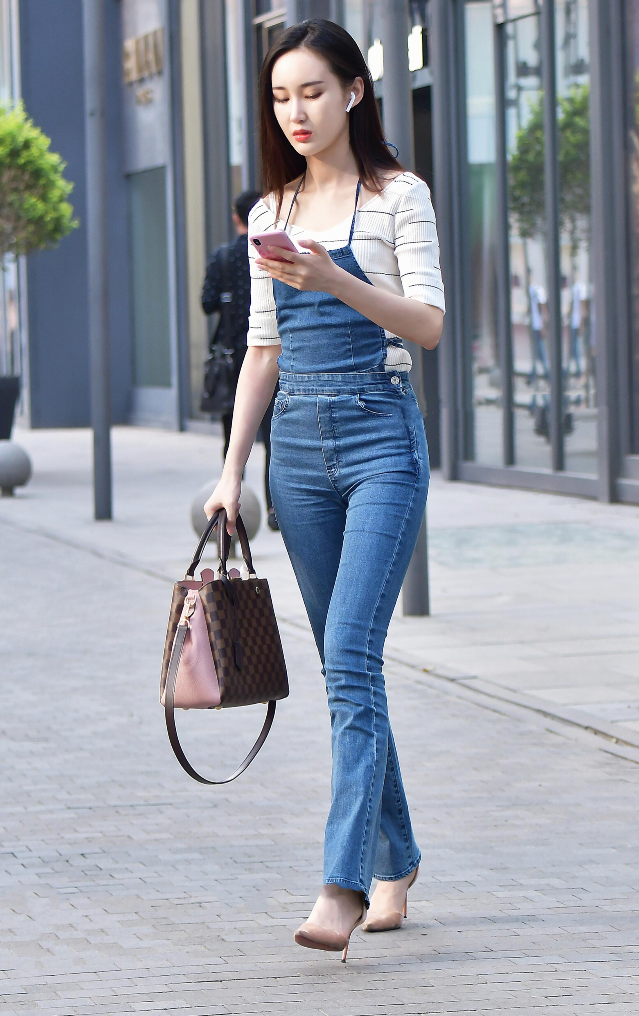 牛仔短裤美少女_街拍美女:小姐姐穿着百搭的背带牛仔裤,秒变大长腿就是这么简单