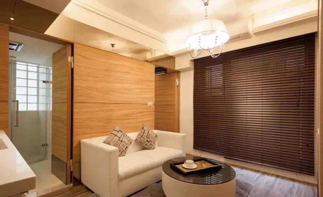 沙发背景墙就是一个木板隐形门设计,左边是卫生间,右边是卧室.