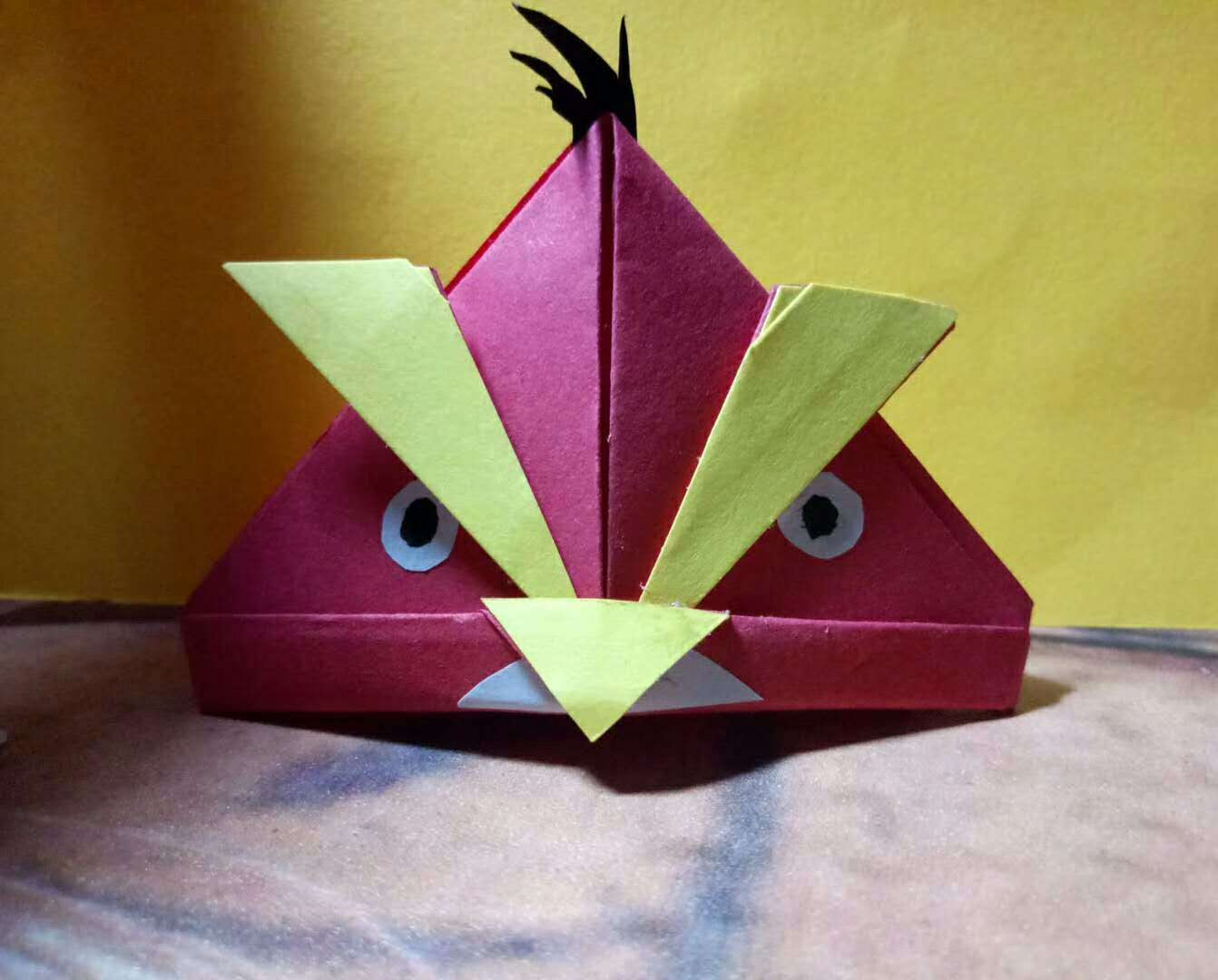 在我一步一步地耐心地讲解、示范和纠正,以及辅导老师的帮忙下,同学们终于把这只可爱的生动的愤怒的小鸟折出来了。再经过最后的加工,上色,小鸟变得栩栩如生,同学们的脸上也露出了灿烂的笑容。看到他们对折纸如此的感兴趣,我很高兴。