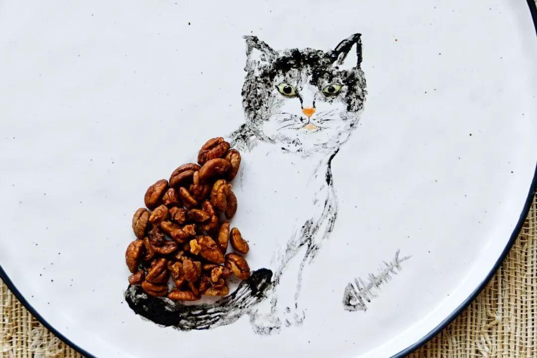 接着取小核桃仁摆放在小猫的背部作花纹装饰,然后用裱花袋装少许沙拉酱,剪一个小口挤画出猫的眼睛,用黑芝麻酱点缀出猫的眼球部分   主盘造型就完成了   葱 油 饼   主食:   白米粥   主 盘 造 型   首先,用小楷毛笔蘸黑芝麻酱画出小猫的身形轮廓