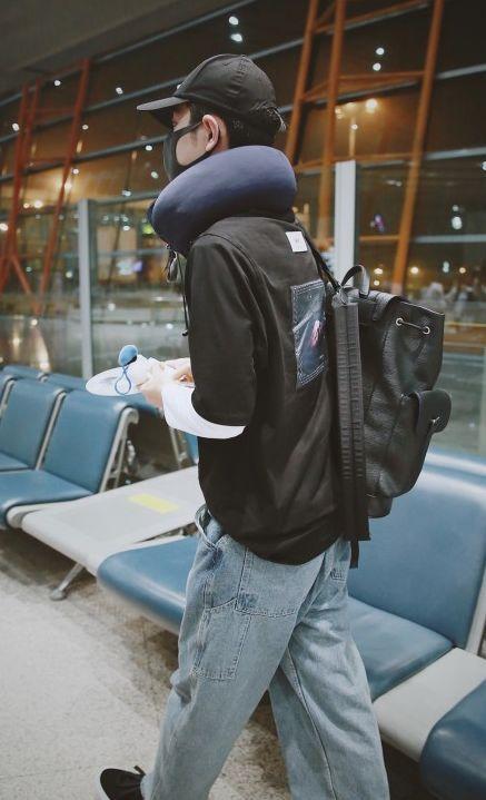 现身机场。他穿粉丝拼接上衣,