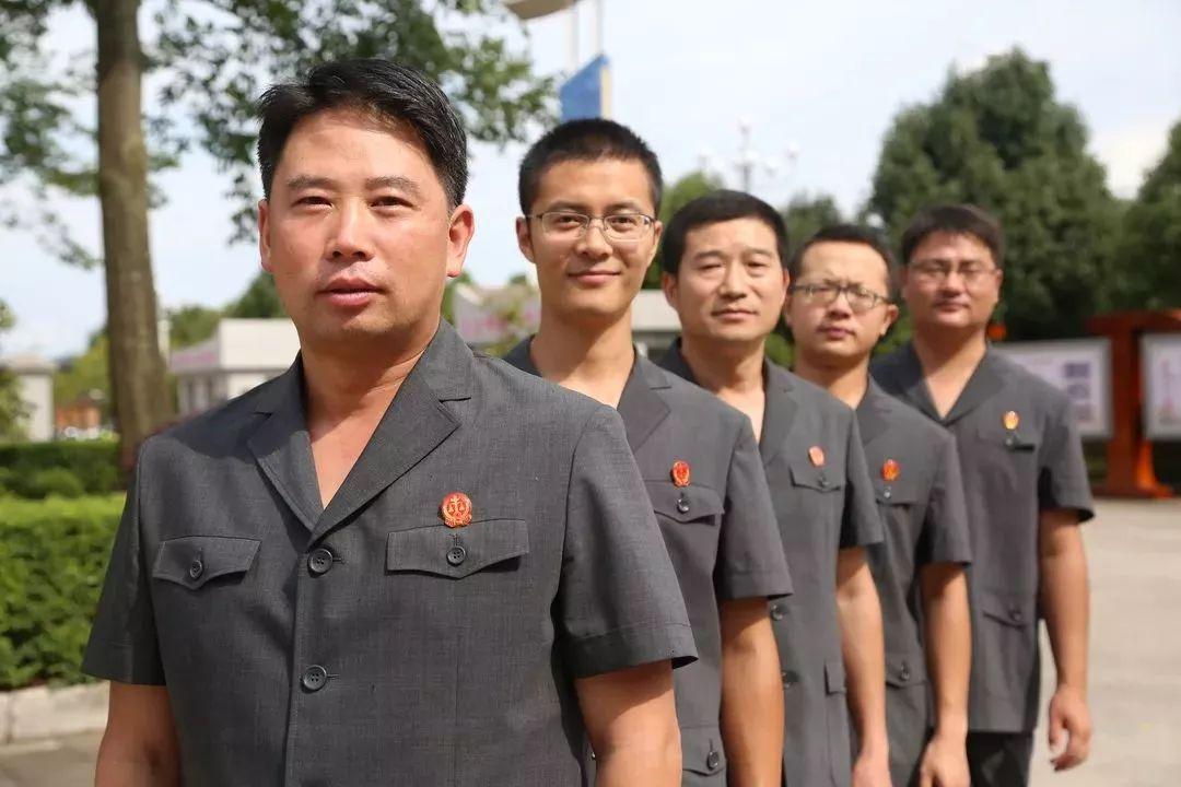 一群自信阳光的活力青年身着新式法官制服步入罗平法院办公大厅,胸前图片