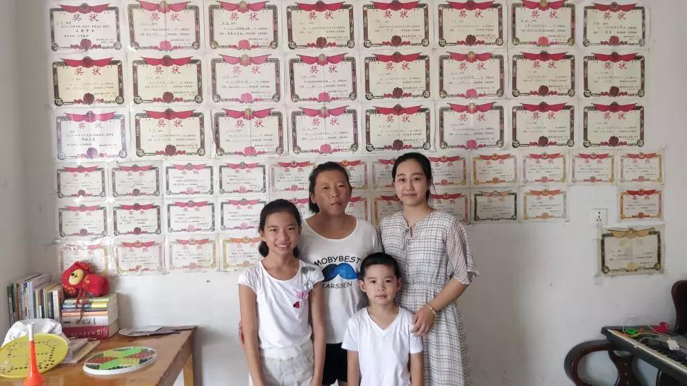王哲老师与学生家人们在奖状墙前合影图片