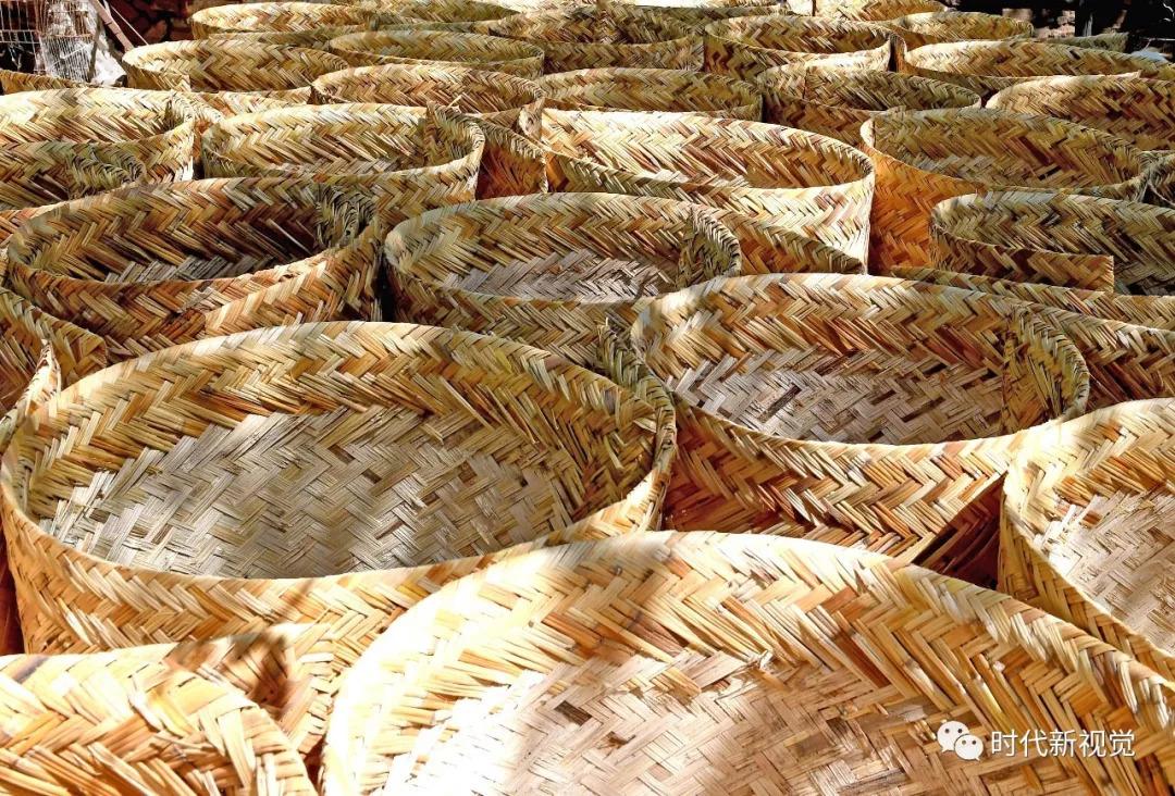 张从来在展示传统手工编织芦席方法.