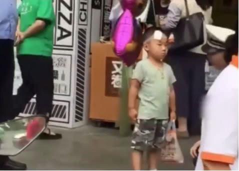 4歲男孩獨自在路邊溜達,頭上裹著紗布,手持父母離婚協議
