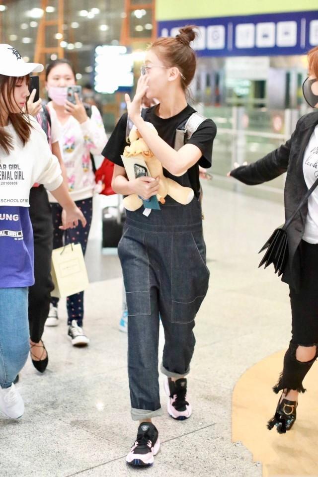 吴谨言机场又穿背带裤,还都搭配黑t恤,但减龄发型却是换不停啊