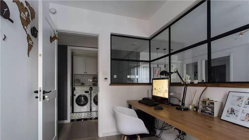 书房空间,局部墙面黑色玻璃隔断通透设计,窗户下实木隔板书桌简洁图片