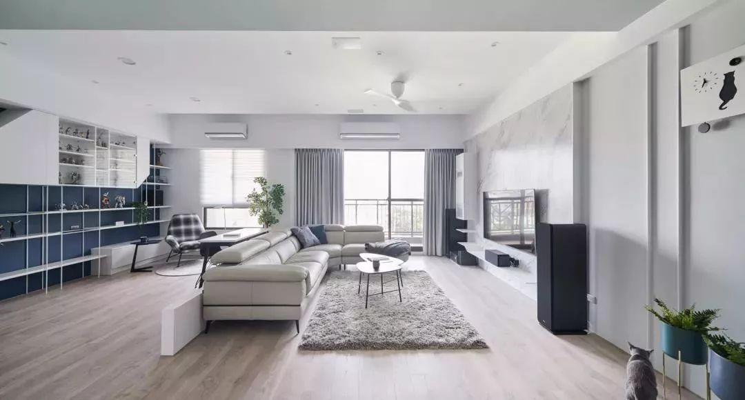 客厅与沙发后的书房以白色矮墙作隔断,空间打通的布局配合简洁利落的图片