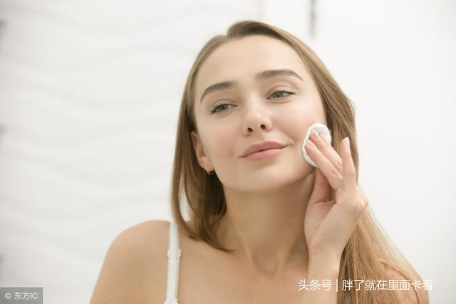 微笑的年輕女士清洗她的皮膚,用化妝棉