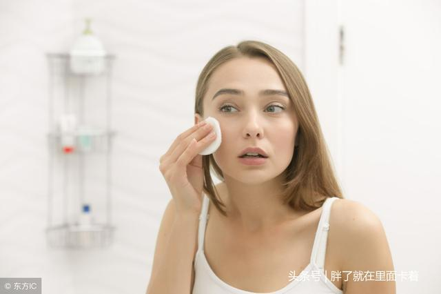 美丽的年轻女子,清洗她的皮肤,用化妆棉