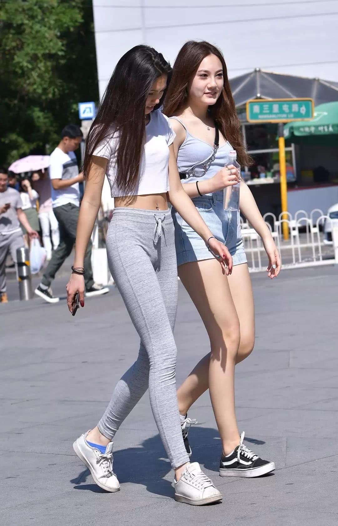 了_街拍:牛仔裤让小姐姐身材更凹凸,这大长腿把短裤闺蜜比了下去