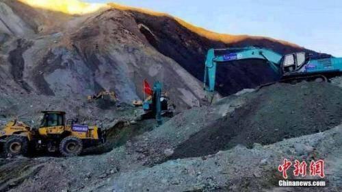 挖掘机等设备在金沙江堰塞湖坝体上开展排险作业.